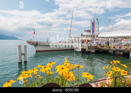 Passengers embarking the elegant restored retro paddle boat named Italie moored at Montreux pier, Lake Geneva (lac Leman), Vaud, Switzerland - Stock Photo