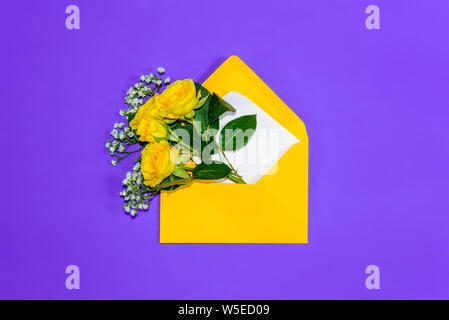 Open envelope with yellow roses and small white filler flowers Gypsophila on purple background. Top view, flat lay. Concept of sending greetings, love - Stock Photo