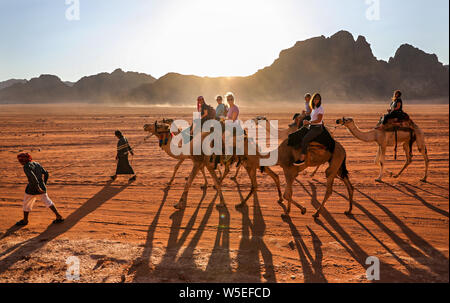 A group of women ride camels guided by Bedouins through the desert of Wadi Rum, Jordan. - Stock Photo