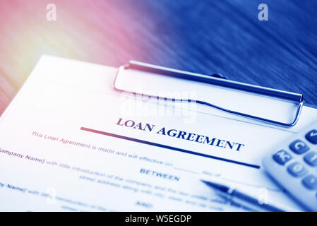 Loan application form with pen and calculator on paper financial help / financial loan negotiation for lender and borrower on business document mortga - Stock Photo