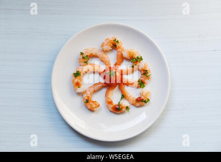 Seafood plate with shrimps prawns ocean gourmet dinner served on plate cooked with ketchup herbs and spices on white wooden background - Stock Photo