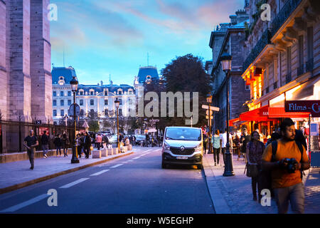 Tourists and locals enjoy an evening out at the shops and cafes on the Ile de la Cite island across from the Notre Dame Cathedral in Paris, France - Stock Photo