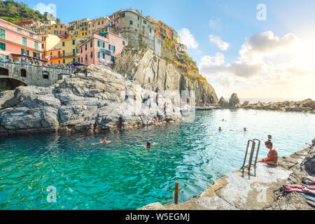 Tourists enjoy a swim in the Ligurian Sea at the village of Manarola, Italy, part of the Cinque Terre, an Unesco World Heritage Site - Stock Photo