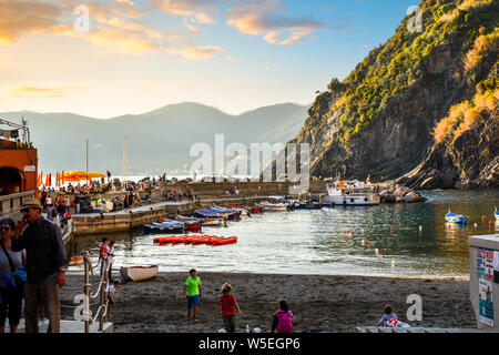 Children play along the sandy beach of Vernazza Italy harbor on the Cinque Terre as tourists enjoy a sunset dinner along the pier. - Stock Photo