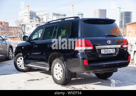 Novosibirsk, Russia - 07.25.2019: Rear view of Toyota Land Cruiser 200 in black color after cleaning before sale in a sunny day on parking - Stock Photo