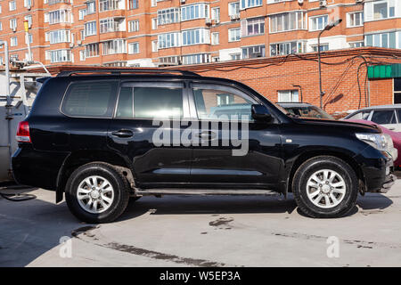 Novosibirsk, Russia - 07.25.2019: Side view of Toyota Land Cruiser 200 in black color after cleaning before sale in a sunny day on parking - Stock Photo