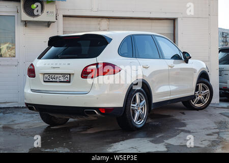 Novosibirsk, Russia - 07.25.2019: Rear view of Porsche Cayenne 958 2008 in white color after cleaning before sale in a summer day on parking backgroun - Stock Photo