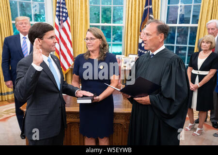 Washington, United States Of America. 23rd July, 2019. President Donald J. Trump looks on during the swearing-in ceremony of the Secretary of Defense Mark Esper Tuesday, July 23, 2019, in the Oval Office of the White House. People: President Donald Trump, Secretary of Defense Mark Esper Credit: Storms Media Group/Alamy Live News - Stock Photo