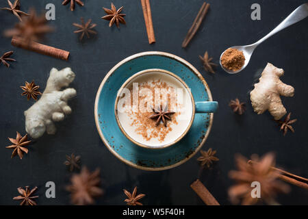 Masala Indian tea in cup with levitation spices and cinnamon on black table. Top view. - Stock Photo