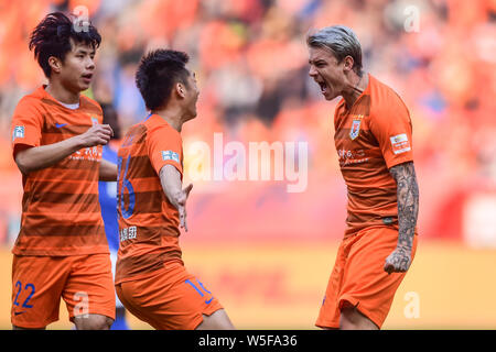 Brazilian football player Roger Krug Guedes, known as Roger Guedes, right, of Shandong Luneng Taishan celebrates with his teammates after scoring agai - Stock Photo