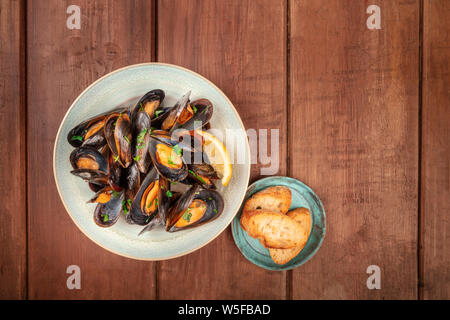 Marinara mussels, moules mariniere, shot from the top on a dark rustic wooden background with toasted bread and a place for text - Stock Photo
