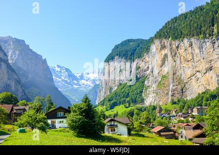 Amazing view of picturesque Lauterbrunnen village with famous Staubbach Falls in background. Popular tourist destination in Switzerland. Summer season, Swiss Alps. Switzerland landscape. - Stock Photo