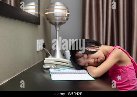 Asian Little Chinese Girl falling alseep while doing homework at home - Stock Photo