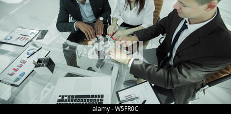 group of business people assembling the pieces of the puzzle - Stock Photo