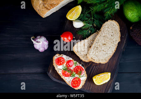 rye bread sandwiches with soft mozzarella or feta cheese and tomatoes on a dark rustic table from old boards - Stock Photo