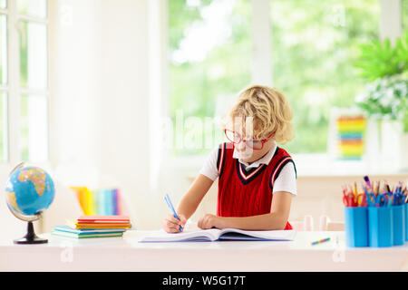 Kids go back to school. Children study and learn for preschool. Little boy of elementary class doing homework. Bedroom with desk, books and globe for - Stock Photo