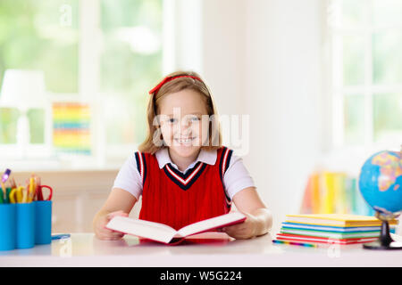 Kids go back to school. Children study and learn for preschool. Little girl of elementary class doing homework. Bedroom with desk, books and globe for - Stock Photo