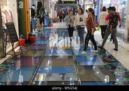 Customers walk on a glass-bottomed walkway at a shopping mall in Zhengzhou city, central China's Henan province, 21 March 2019.    A glass-bottomed wa - Stock Photo