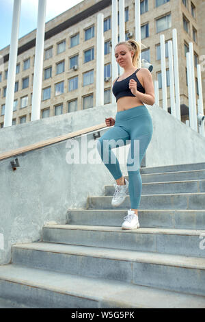 Running in the city sport motivation. Young sporty woman running upstairs on city stairs. - Stock Photo