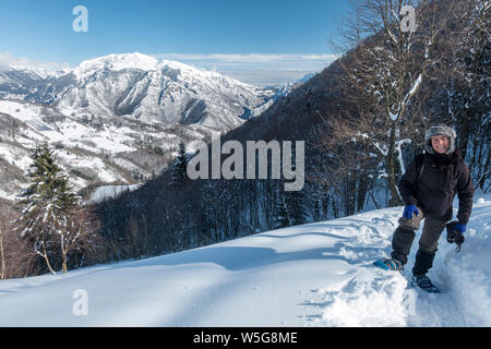 Italy, Lombardy, Orobie Alps Regional Park, snowshoeing on the trail to Grialeggio Pass: Brembana Valley and Mt. Menna covered with snow - Stock Photo