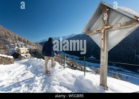 Italy, Lombardy, Retiche Alps, Camonica Valley, snowshoeing on the trail to the ancient alpine church of San Clemente - Stock Photo
