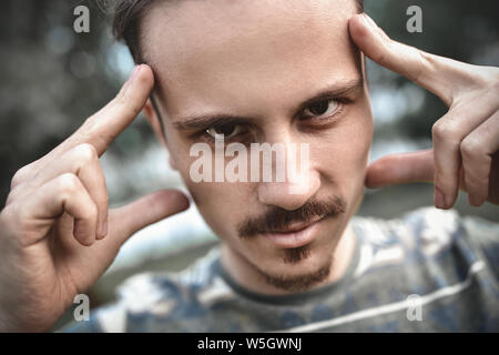 mind games and brain power. mentalist and cognitive skills concept. man concentrating and holding index fingers on temples. young bearded guy portrait - Stock Photo