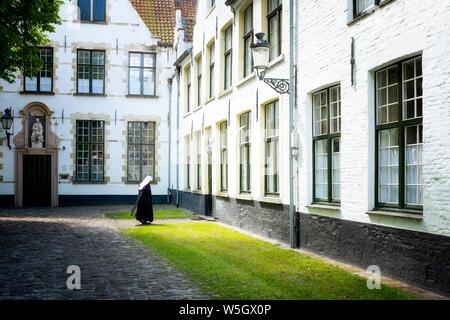 Nun at Begijnhof (Beguinage), Order of St. Benedict Convent, UNESCO World Heritage Site, Bruges, Belgium, Europe - Stock Photo