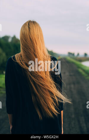 Woman with very long hair standing back to camera on country road - Stock Photo