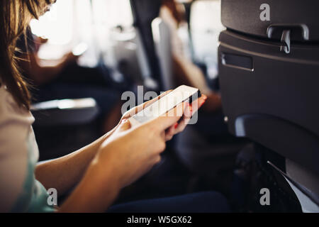 Young woman using smartphone during flight - Stock Photo