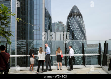Office workers viewing buildings in the City of London from the garden terrace at 120 Fenchurch Street in summer 2019  London UK  KATHY DEWITT - Stock Photo