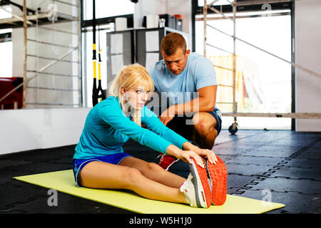 Photo of a woman doing some stretching exercises with her trainer - Stock Photo