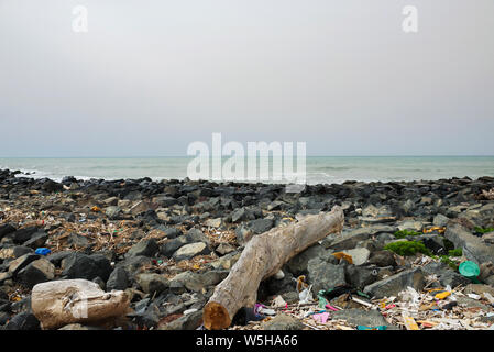 Spilled garbage on the beach near the big city. Empty used dirty plastic bottles and other garbage. Environmental pollution. Ecological problem. - Stock Photo