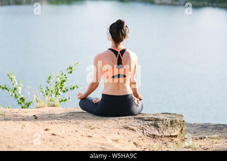 Rear view of young woman in wireless headphones sitting in lotus position