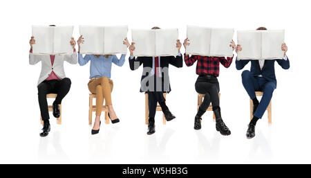 group of five young people sitting and reading newspapers, all covering their faces with the newspaper, on white background - Stock Photo
