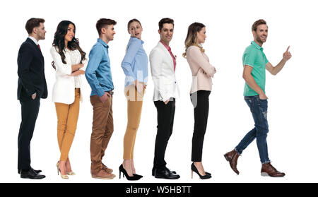 happy casual man stepping out of a line of people and points finger on white background - Stock Photo