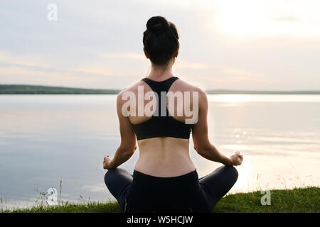Rear view of young woman in black sportswear sitting with crossed legs - Stock Photo