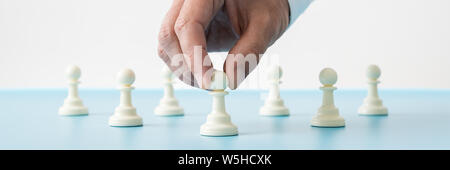 Wide view image of male hand holding the first of many pawn chess pieces placed on blue desk in a conceptual image.