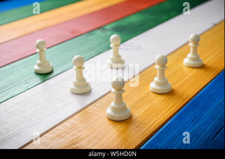 White pawn chess pieces placed on a coulourful desk of wooden planks. - Stock Photo