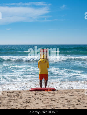 A lifeguard patrolling on the beach during summertime is putting in place a warning sign for swimmers venturing into the ocean - Stock Photo