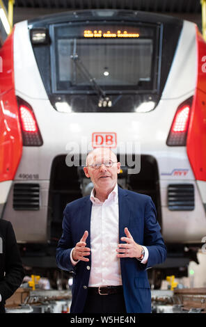 Hamburg, Germany. 29th July, 2019. Michael Westhagemann (non-party), Hamburg Senator for Economic Affairs, speaks during his visit to the new Stellingen S-Bahn maintenance plant. In the background is a class 490-618 train. Credit: Daniel Reinhardt/dpa/Alamy Live News - Stock Photo