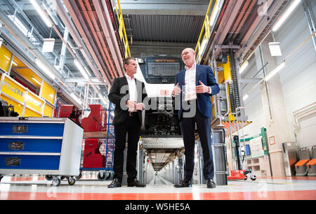 Hamburg, Germany. 29th July, 2019. Michael Westhagemann (r, non-party), Hamburg Senator for Economic Affairs, and Kay Uwe Arnecke, Managing Director of S-Bahn Hamburg, speak during a visit by the Senator to the new Stellingen S-Bahn maintenance plant. In the background is a class 490-618 train. Credit: Daniel Reinhardt/dpa/Alamy Live News - Stock Photo