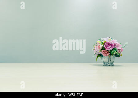 Plastic flowers in pots placed on desks and backgrounds with copy space for text. - Stock Photo
