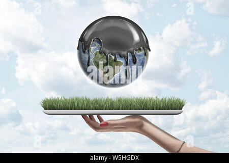 Female hand holding earth globe covered with black thick liquid on green grass model on blue sky background - Stock Photo