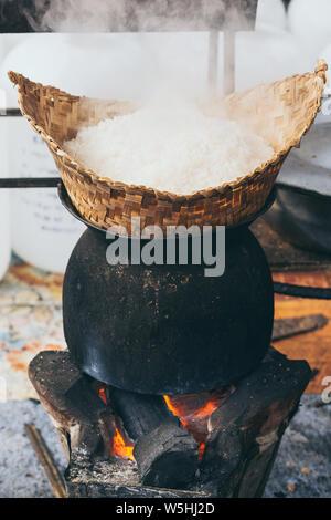 White laotian steam rice cooking on wood burning stove in Luang Prabang, Laos. Vertical orientation - Stock Photo