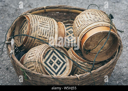 Traditional Laotian decorated rice baskets used for sacred Buddhist alms giving ceremony in Luang Prabang city, Laos. - Stock Photo