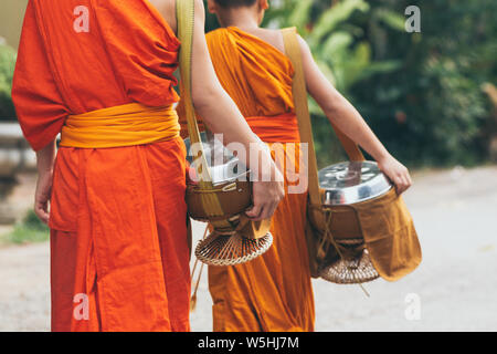 Buddhist monks during Laotian traditional sacred alms giving ceremony in Luang Prabang city, Laos. - Stock Photo