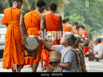 Laotian people making offerings to Buddhist monks during traditional sacred alms giving ceremony in Luang Prabang city, Laos. - Stock Photo