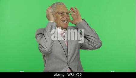 Elderly businessman in suit laughing. Old senior man in formal wear on chroma key background. Place for your logo or text. Green screen background - Stock Photo