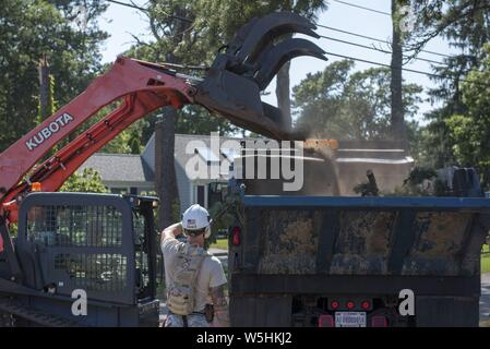 Airmen from the Massachusetts Air National Guard's 102nd Civil Engineer Squadron mobilized to support recovery efforts in the wake of two tornadoes that touched down on Cape Cod on July 23, 2019, July 25, 2019. The Airmen cleared fallen trees and debris from roadways in the towns of Dennis and Harwich Massachusetts. Image courtesy Tech. Sgt. Thomas Swanson/102nd Intelligence Wing. () - Stock Photo