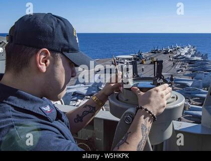 190725-N-DL524-0055 CORAL SEA (July 25, 2019) Quartermaster 3rd Class Payton Sanchez, from Corpus Christi, Texas, obtains the sun's azimuth at the forward lookout station aboard the Navy's forward-deployed aircraft carrier USS Ronald Reagan (CVN 76), July 25, 2019. Ronald Reagan, the flagship of Carrier Strike Group 5, provides a combat-ready force that protects and defends the collective maritime interests of its allies and partners in the Indo-Pacific region. (U.S. Navy photo by Mass Communication Specialist 3rd Class Erica Bechard) Image courtesy Petty Officer 3rd Class Erica Bechard/USS RO - Stock Photo